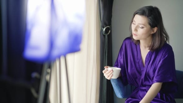 Thumbnail for Woman At The Window Drinking a Cup Of Coffee