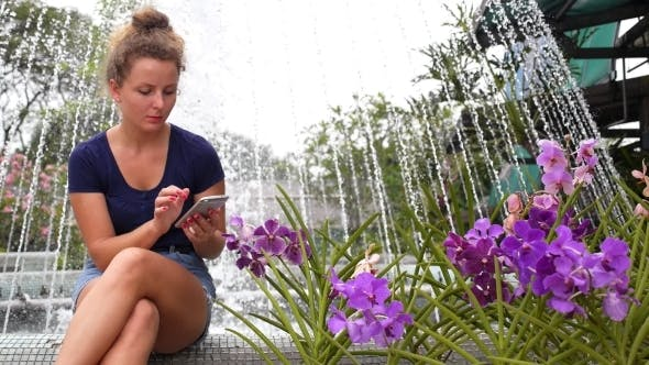 Thumbnail for Young Pretty Girl Using Mobile Phone In Summer Park.