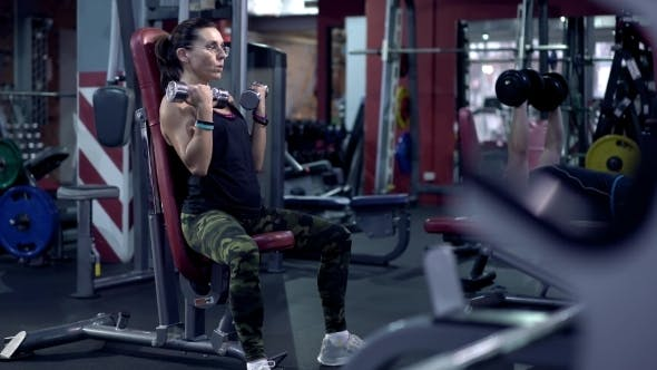 Thumbnail for Athletic Woman Pumping Up Muscules With Dumbbells