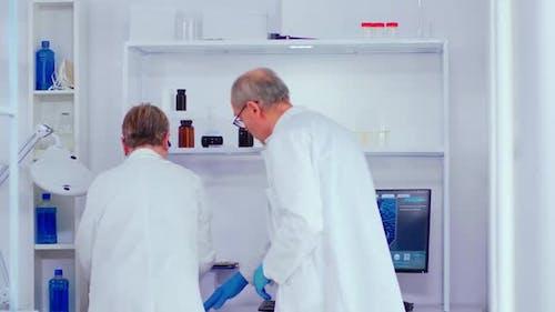 Elderly Biochemists Working in Modern Laboratory