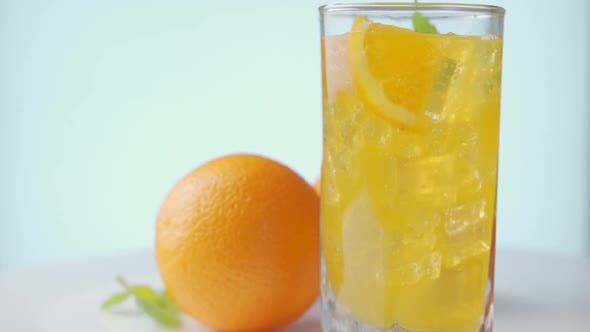 Thumbnail for Rotating of Glass with Summer Healthy Lemonade, Cocktail of Orange, Ice and Mint.