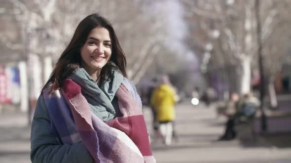 Thumbnail for Glamour Girl in a Stylish Scarf Smiling in a Sunny Alley in Winter in Slow Motion