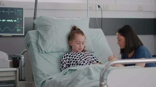 Worried Mother Sitting Beside Little Daughter Praying While Sleeping After Illness Surgery