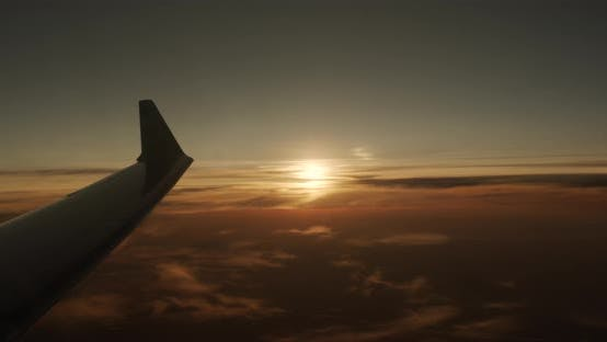 Thumbnail for Wing of an Airplane Flying Above the Clouds with Sunset Sky, View From the Window of the Plane