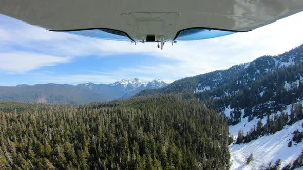 Thumbnail for Snowy Cascade Mountains Aerial Flying View Above Sunny Forest From Camera Mounted Under Helicopter