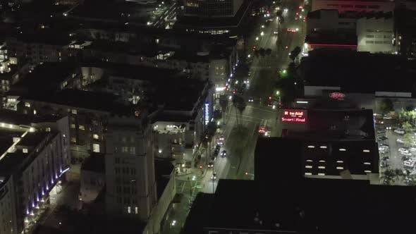Thumbnail for AERIAL: Over Wilshire Boulevard in Hollywood Los Angeles at Night with Glowing Streets and City Car