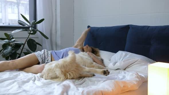 Female with Retriever Dog Awaking in Bedroom