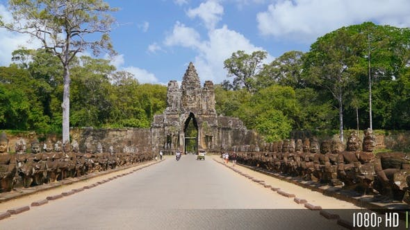 Thumbnail for Bayon Angkor Thom Entrance Gate as Tourists Walk and Ride by