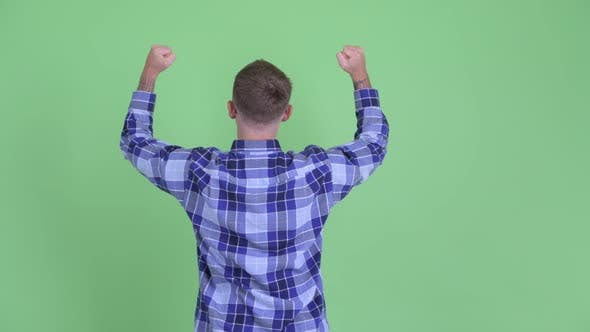 Thumbnail for Rear View of Happy Hipster Man with Fists Raised