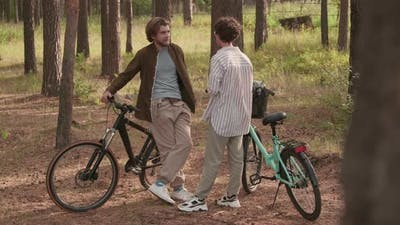 Couple Of Friends On Bikes In Woods