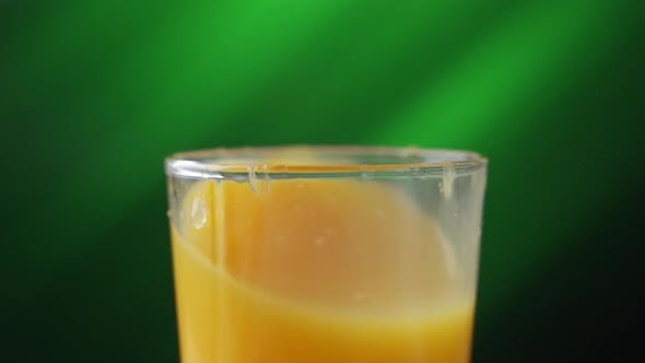 Thumbnail for Glass with Orange Juice. Ice Cube Fall, Creating a Lot of Splashing. Slow Motion