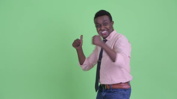 Cover Image for Happy Young African Businessman Looking Excited While Showing To Back
