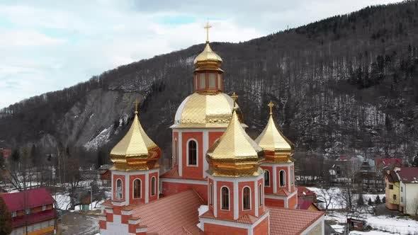 Thumbnail for LuftDrohne Ansicht der ukrainischen Kirche mit goldenen Kuppeln im Karpatendorf im Winter