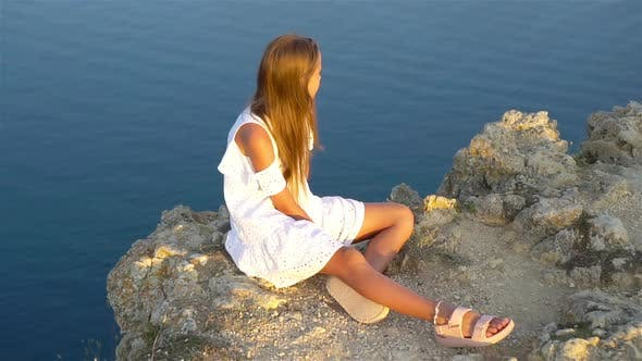 Little Girl on Top of a Mountain Enjoying Valley View Before Sunset
