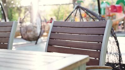 Empty Seat and Wooden Table in Outdoor Cafe