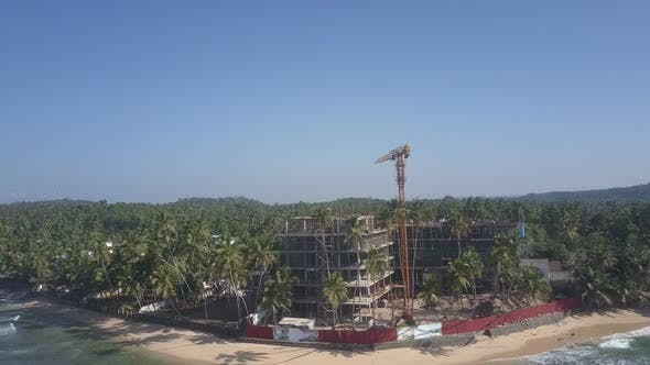 Crane on Construction Territory Between Forests and Ocean