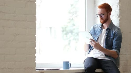 Man with Beard and Red Hairs Using Tablet for Work and Browsing Information