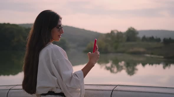 Woman Enjoying River Scene at Sunset and Taking Pictures with Mobile