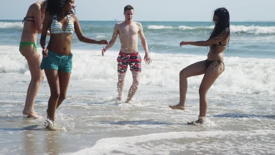 Happy young group of multi ethnic friends kicking splashing water on the beach