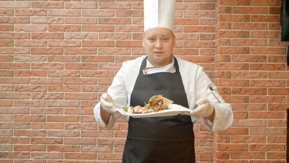 Thumbnail for Friendly chef in uniform present a plate with seafood salad