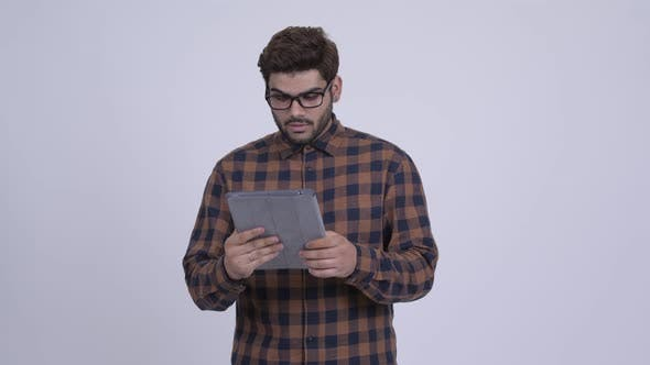 Thumbnail for Stressed Young Indian Hipster Man Using Digital Tablet and Looking Shocked