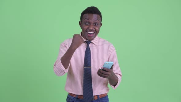 Thumbnail for Happy Young African Businessman Using Phone and Getting Good News
