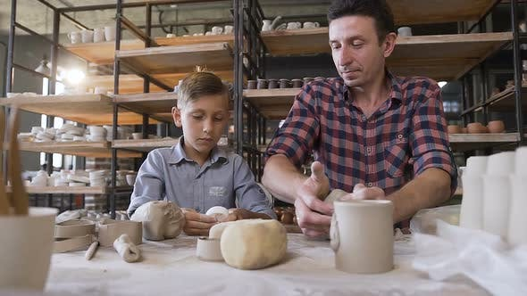 Thumbnail for Little Boy Making Part of Pots while His Father Kneading Clay
