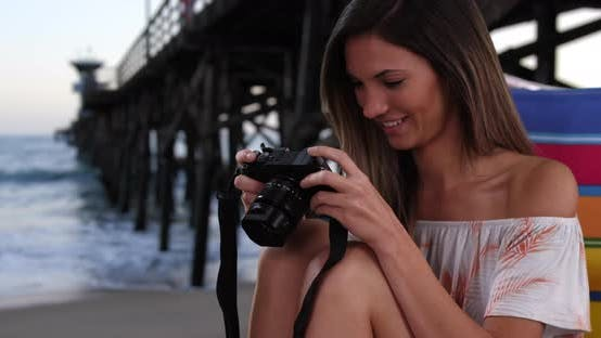 Thumbnail for Young female photographer in her 20s sitting in chair at beach next to pier