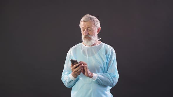 Thumbnail for Old Doctor Chatting on Smartphone. Portrait of Old Man