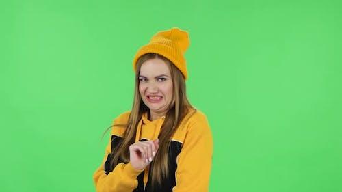 Porträt des modernen Mädchens in gelbem Hut hält die Palme zusammen und bittet um etwas.  Grün