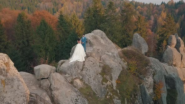 Newlyweds Stand on a High Slope of the Mountain, Groom and Bride, Arial View