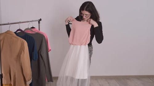 Beautiful Young Girl Standing at the Clothes Rack Picking Up Clothes Basic Wardrobe
