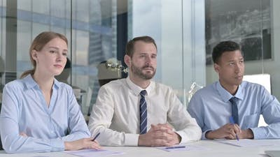 Middle Aged Businessman Giving Introduction with Assistants on Office Table