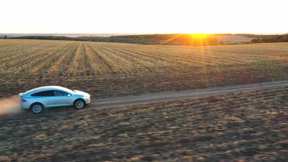 Thumbnail for Aerial View of Electrical Car Moving Through Dusty Route. Drone Tracking Modern Vehicle Driving