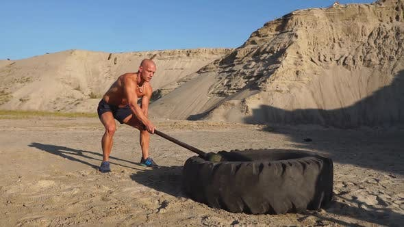 Thumbnail for Muscle Athlete Strongman Man Hits a Hammer on a Huge Wheel in the Sandy Mountains