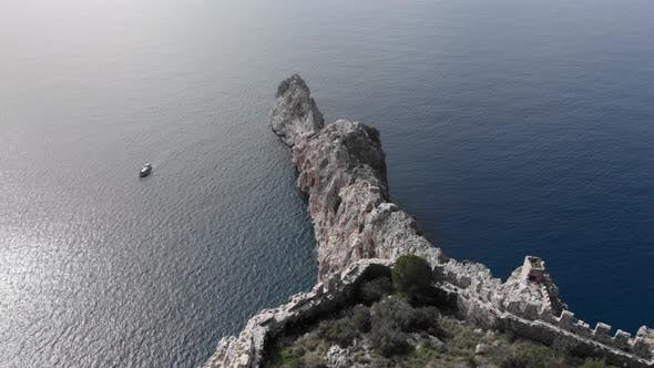 Remains of fortress on cliff of rocky mountains in sea