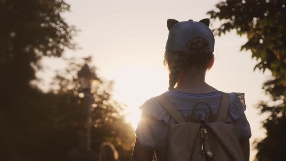 Thumbnail for A Child with a Backpack Is Standing in the Park
