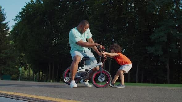 Thumbnail for La famille africaine avec enfant s'amuse à vélo