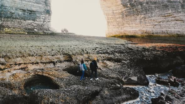 Thumbnail for Happy Tourist Man Helping Woman Get Onto Big Low Tide Sea Shore Coral Rock Under Giant Natural Arch