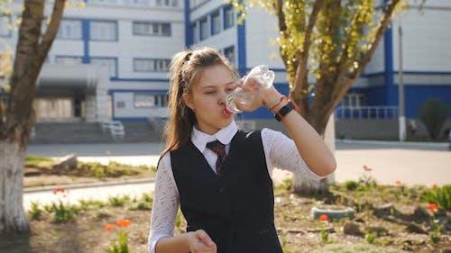 Schoolgirl Teenager in School Uniform Drinks Water From a Plastic Bottle Near the School