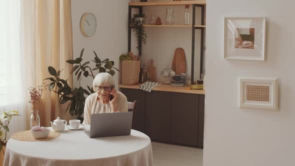 Thumbnail for Senior Woman Sitting with Laptop and Chatting on Phone