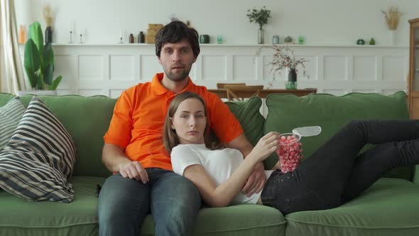 Young Couple Watching Tv with Popcorn on Couch