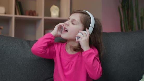 Thumbnail for Little Girl Listens To Music On Wireless Headphones