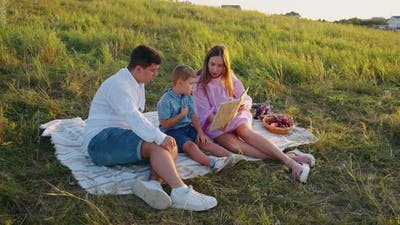 Mother Reading Book to Son at Picnic