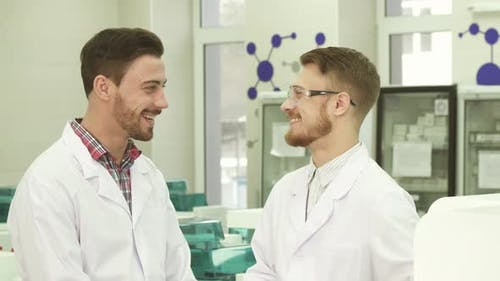 Two Laboratory Technicians Communicate on Working Subjects