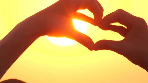 Thumbnail for Shaping Heart with Hands Over the Sunset Sunrise By the Ocean or Sea. High Quality Video of Symbol