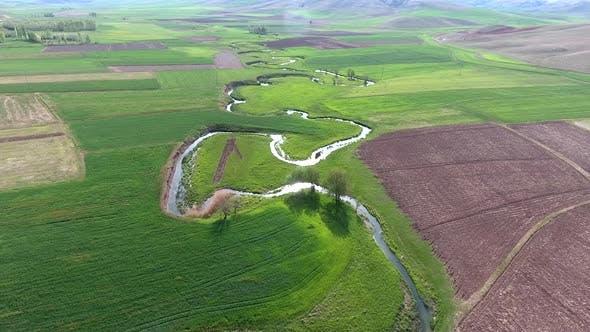 Meander Stream Between The Fields in Wide Valley