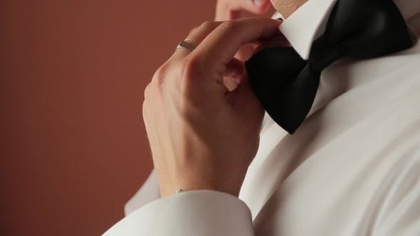 Thumbnail for A Man In a White Shirt Dresses Black Tie