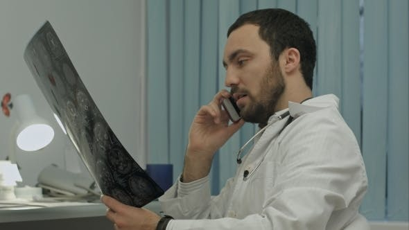 Thumbnail for Male Doctor Talking On Cellphone At Modern Hospital Indoors