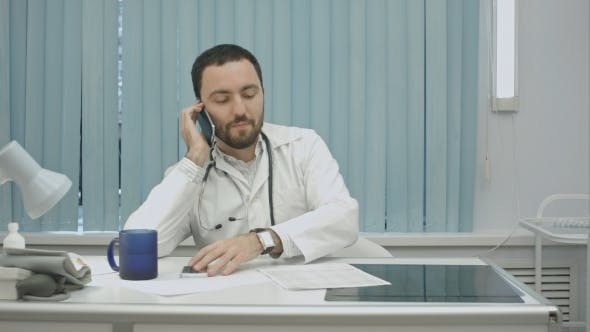 Thumbnail for Male Doctor Speaking On Cellphone At Modern Hospital Indoors